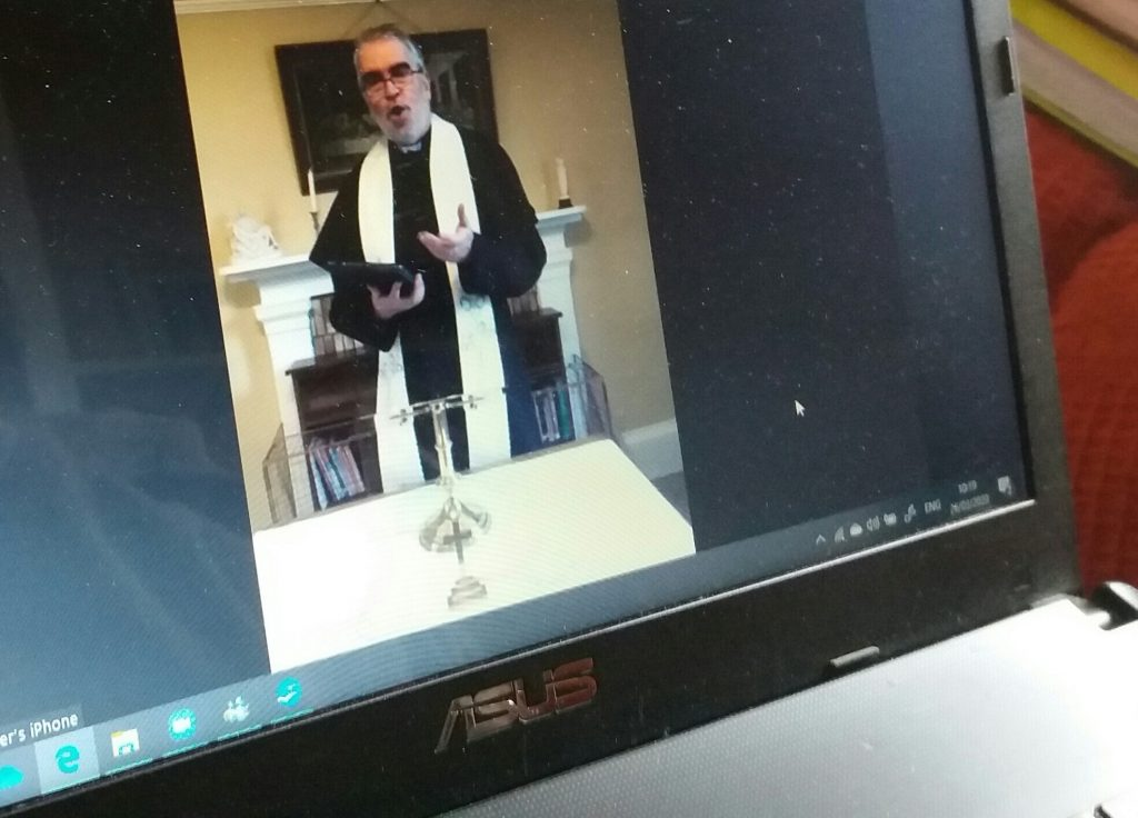 A picture of a computer monitor showing Fr Chris conducting a service